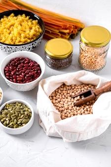Pâtes, lentilles, graines de citrouille, pois chiches et haricots dans des bols.
