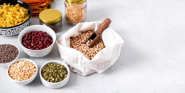 Pâtes, lentilles, pois chiches et haricots dans des bols. copiez l'espace.