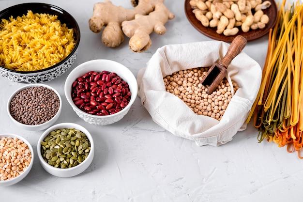 Pâtes, lentilles, racine de gingembre, pois chiches et haricots dans des bols.