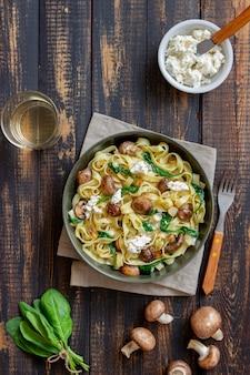 Pâtes linguines aux champignons, fromage blanc, épinards et ail. alimentation équilibrée. la nourriture végétarienne. régime.