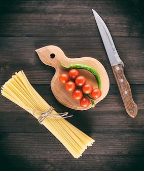 Pâtes longues italiennes crues et tomates cerises rouges bien mûres