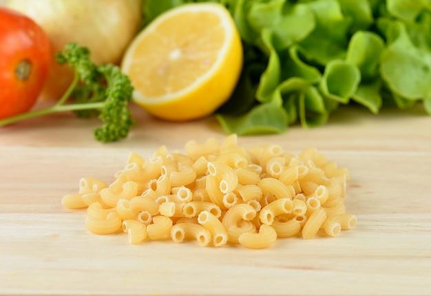 Pâtes macaroni bouchent sur table en bois