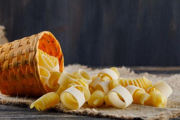 Pâtes macaroni dans un petit seau sur un sac et un fond sombre. vue de côté. espace libre pour votre texte