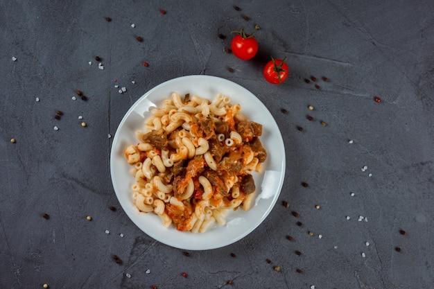 Pâtes, macaronis à la viande et à la sauce servis sur la plaque blanche sur le fond texturé gris.