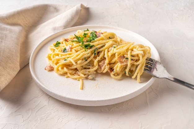 Pâtes maison classiques italiennes carbonara avec bacon, œufs, parmesan sur plaque en céramique légère avec fourchette et serviette sur table lumineuse. vue rapprochée