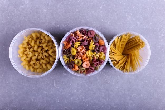 Pâtes multicolores additionnées de colorant végétal naturel. dans un pot sur une table en béton