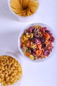 Pâtes multicolores additionnées de colorant végétal naturel. dans un pot sur une table blanche
