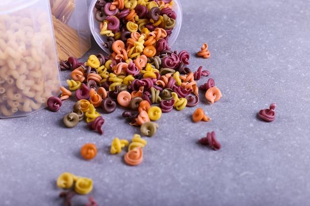 Pâtes multicolores additionnées de colorant végétal naturel. dispersé d'une canette sur une table en béton