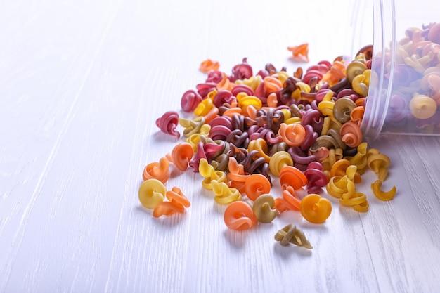 Pâtes multicolores additionnées de colorant végétal naturel. dispersé de la canette sur la table blanche