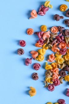 Pâtes multicolores additionnées de colorant végétal naturel. dispersé sur un fond bleu. vue de dessus, modèle.