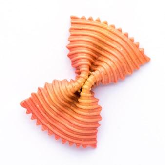 Pâtes noeud papillon de couleur. gros plan unique orange farfalle isolé.