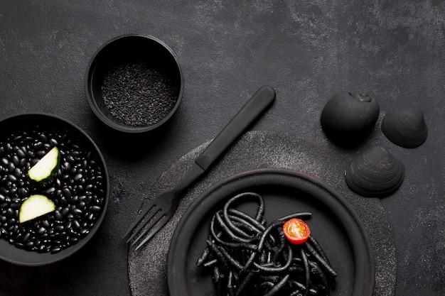 Pâtes noires aux crevettes avec palourdes et graines vue de dessus