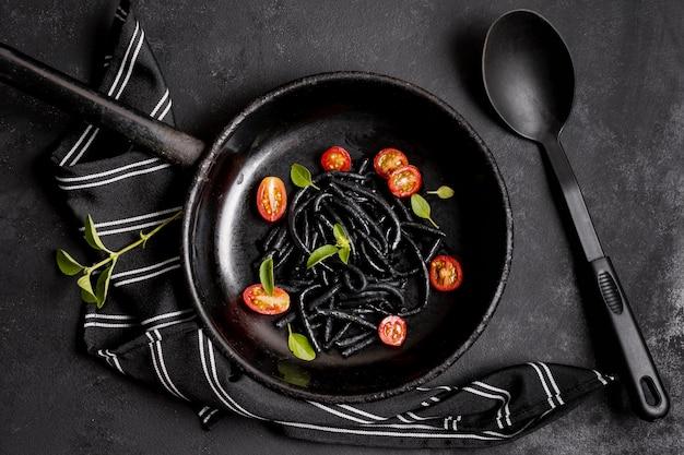 Pâtes noires aux crevettes et serviette de cuisine avec cuillère