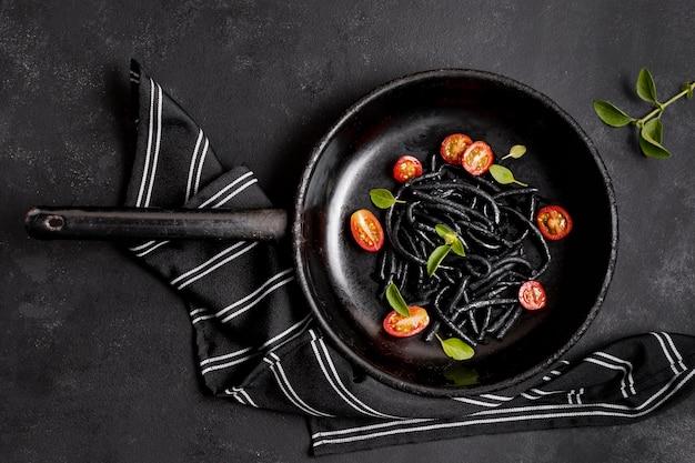 Pâtes noires aux crevettes et serviette de cuisine