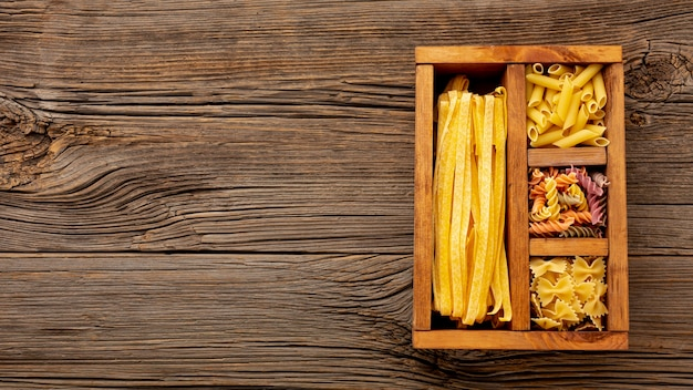 Pâtes non cuites dans une boîte en bois avec espace de copie