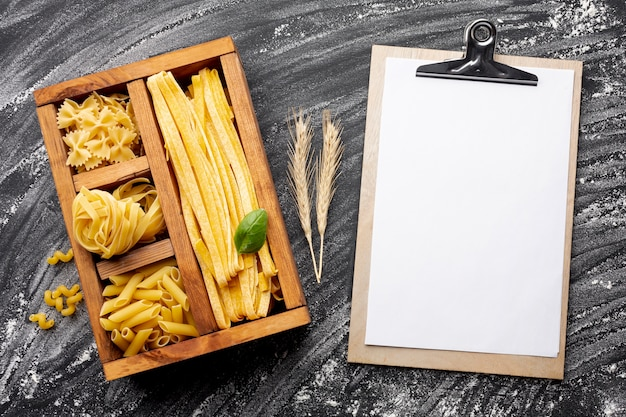 Pâtes non cuites dans une boîte en bois avec maquette du presse-papiers