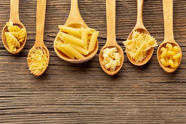 Pâtes non cuites dans des cuillères en bois
