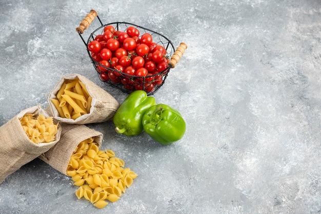 Pâtes non cuites dans un sac rustique avec tomates cerises et poivrons sur table en marbre.