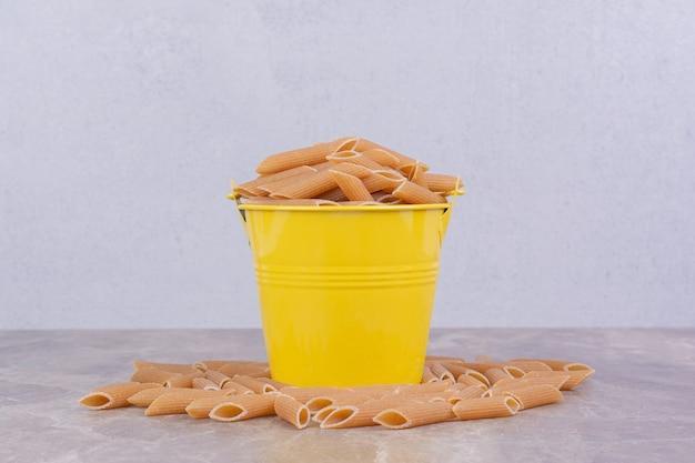 Pâtes non cuites dans un seau métallique jaune.