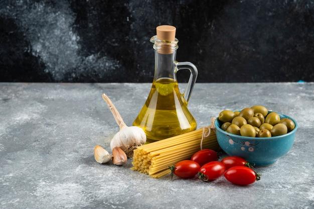 Pâtes non cuites, huile et légumes frais sur table en marbre.