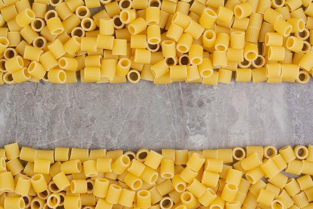Pâtes non cuites isolées sur l'espace en marbre.
