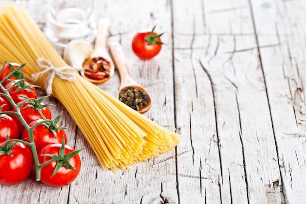 Pâtes non cuites avec des tomates et des épices
