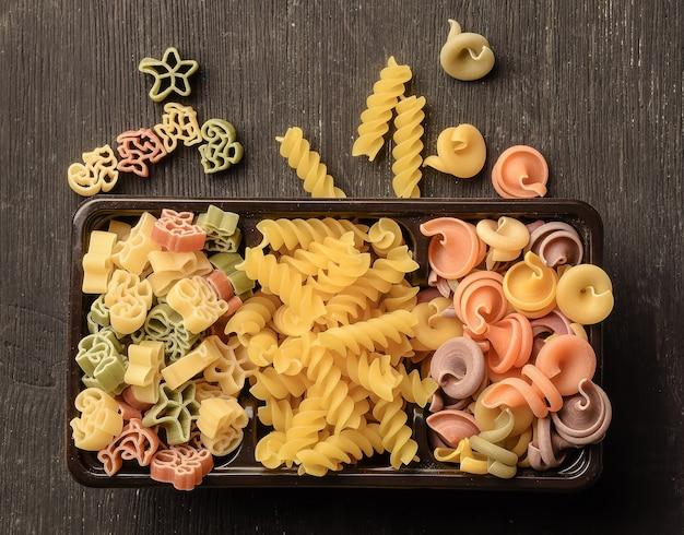 Les pâtes et les nouilles de différents types et couleurs se trouvent dans une boîte sur une table en bois. certains d'entre eux sont dispersés près de la boîte