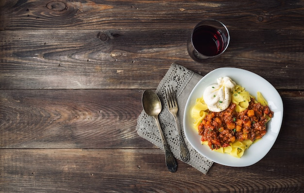 Pâtes pappardelle avec ragoût de viande à la citrouille et fromage burrata sur table en bois rustique. cuisine italienne. vue de dessus. copiez la zone d'espace.