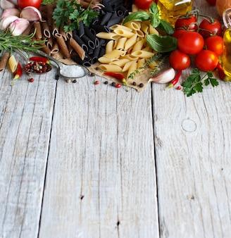 Pâtes penne aux légumes, herbes et huile d'olive sur table en bois