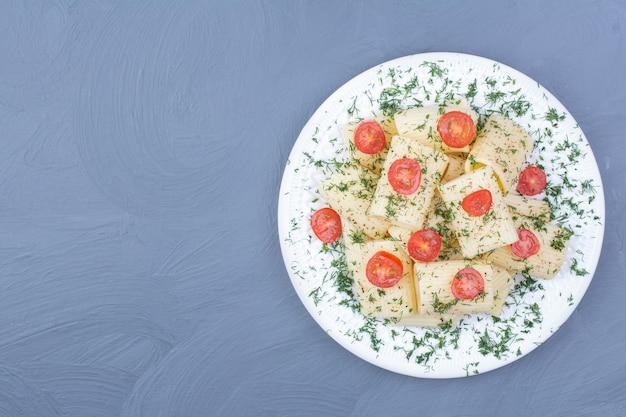 Pâtes penne aux tomates cerises et herbes hachées dans une assiette blanche.