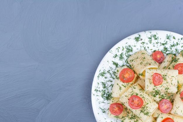 Pâtes penne aux tomates et épices dans une assiette blanche
