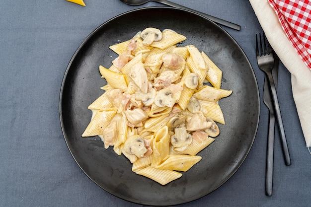 Pâtes penne à la confiture, poulet et champignons sous parmesan
