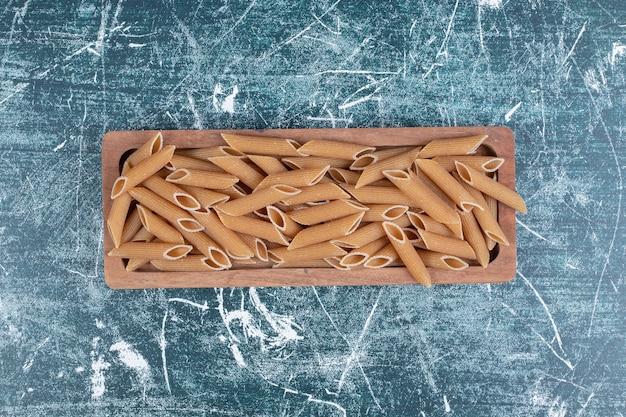 Pâtes penne crues non cuites sur plaque en bois. photo de haute qualité