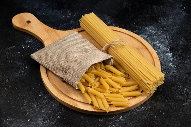 Pâtes penne dans un panier rustique avec des spaghettis sur un plateau en bois.