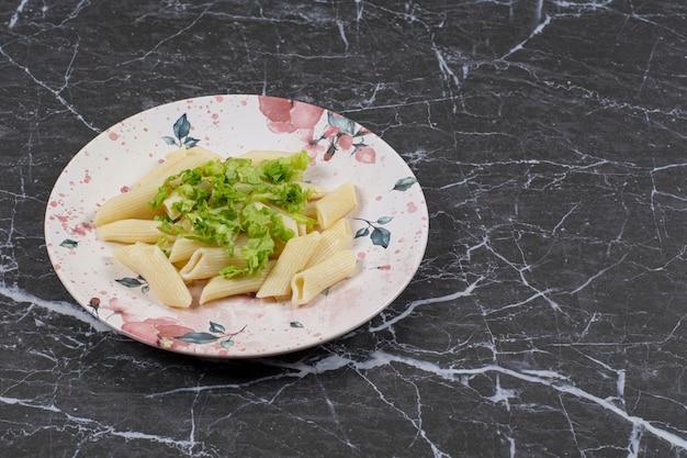Pâtes penne avec sauce aux légumes sur plaque blanche.