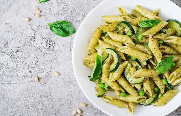 Pâtes penne à la sauce pesto, courgettes, petits pois et basilic. nourriture italienne. vue de dessus. mise à plat