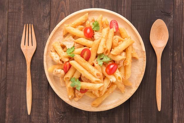 Pâtes penne à la sauce tomate au poulet sur une table en bois