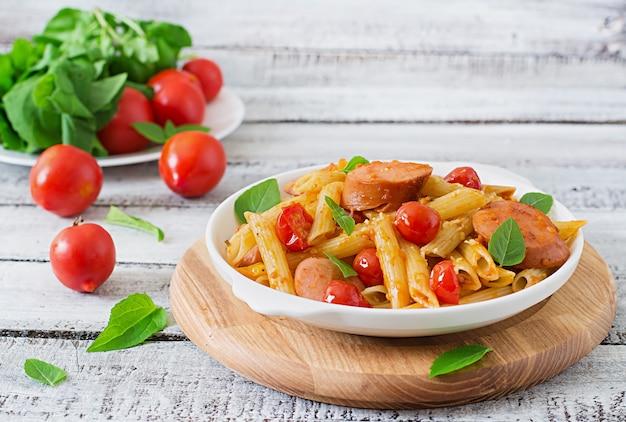 Pâtes penne à la sauce tomate avec saucisse, tomates, basilic vert décorées dans une poêle sur une table en bois