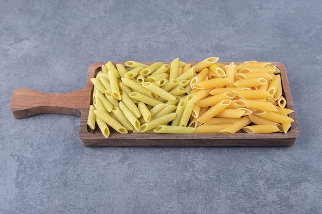 Pâtes penne vertes et jaunes crues sur planche de bois.