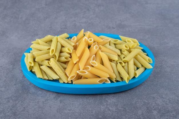 Pâtes penne vertes et jaunes crues sur plaque bleue.