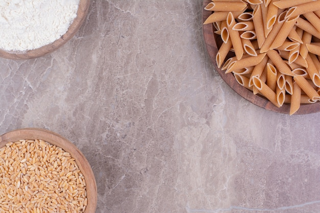 Pâtes sur un plateau en bois avec du blé et de la farine dans des tasses en bois.