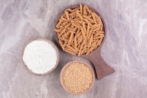 Pâtes sur un plateau en bois avec du blé et de la farine mélangée dans des tasses