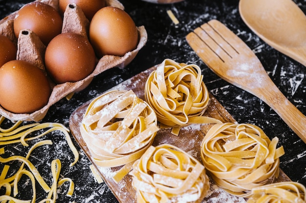 Pâtes près des œufs et des ustensiles