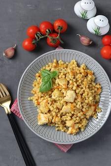 Pâtes ptitim faites maison avec du poulet et des légumes sur une table gris foncé. vue de dessus. format vertical.
