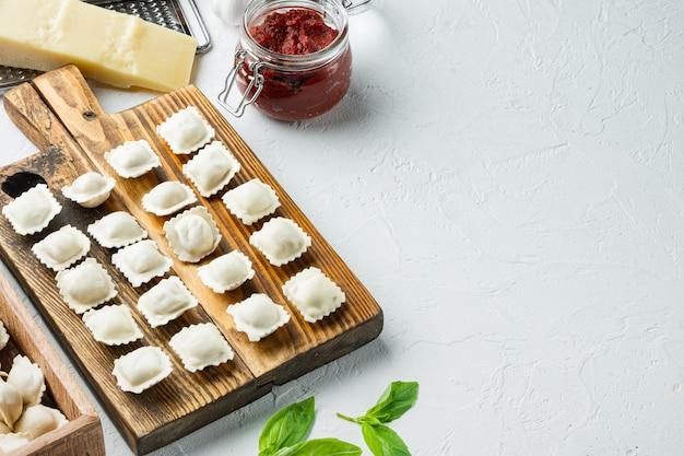Pâtes raviolis italiens frais faits maison sur planche de bois, sur fond blanc,