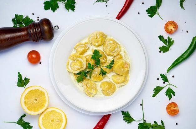Pâtes raviolis traditionnels italiens avec de la viande ou du poisson d'esturgeon sur fond blanc