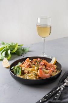 Pâtes reginelle aux fruits de mer, crevettes, moules en plaque noire sur table en pierre grise, gros plan. plat traditionnel dans un restaurant italien.