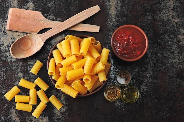 Pâtes rigatoni non cuites dans un bol. sauce tomate et épices. spatule et cuillère en bois. concept de cuisson des pâtes à la sauce tomate. vue de dessus. mise à plat.