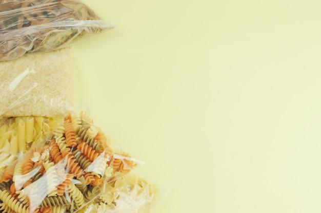 Pâtes, riz sur fond jaune. livraison de nourriture, don ou concept de stock.