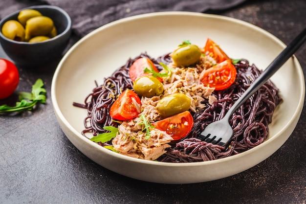 Pâtes de riz noir au thon, tomates et olives dans une assiette blanche